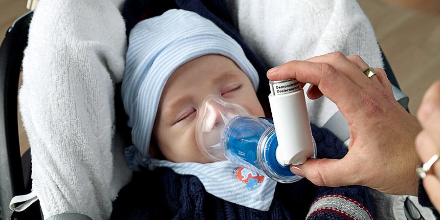 Baby inhaliert mit Inhalierhilfe